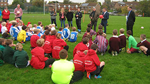 National Children's Football Alliance's Ernie Brennan presents Chailey School with a Peace Poppy Ball to kick off the Peace Fields Tournament